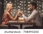 beautiful young couple is... | Shutterstock . vector #748493203