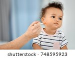 mother feeding baby with spoon... | Shutterstock . vector #748595923