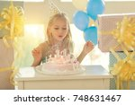 little birthday girl blowing... | Shutterstock . vector #748631467