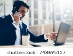 man with laptop and smartphone... | Shutterstock . vector #748695127