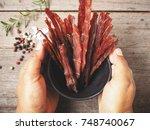 beef jerky on hands | Shutterstock . vector #748740067
