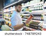 a handsome bearded man chooses... | Shutterstock . vector #748789243
