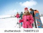 smiling girl with family on ski ... | Shutterstock . vector #748859113