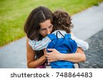a woman hugs a curly haired boy ... | Shutterstock . vector #748864483