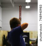 Small photo of Preteen archer uses compound bow to aim arrow at distant fixed target. Archery is one of the oldest practices in existence for hunting and before that a tool for protection.