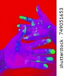 Small photo of Purple hand stained green on Red background , Hand in Gamma radiation /gamma ray effect , neon effect