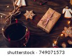 Small photo of Decorated christmas gift with gingerbread cookies, nuts, cinnamon, glass of punch, anis on old wooden table, decorated by festive decor. Dark rustic style.