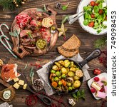 Small photo of Delicious Christmas themed dinner table with roasted meat steak, appetizers and desserts. Top view. Flat lay with holiday concept.