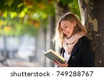 happy young woman reading a... | Shutterstock . vector #749288767