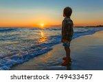 little boy watching the sunset... | Shutterstock . vector #749433457