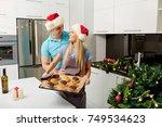 couple in santa's hats in the... | Shutterstock . vector #749534623