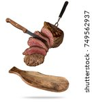 flying beef steaks served on... | Shutterstock . vector #749562937