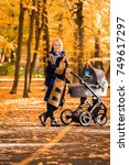 a young mother with a stroller... | Shutterstock . vector #749617297