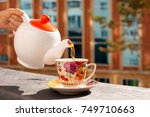 the tea is poured into a cup.... | Shutterstock . vector #749710663