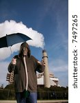 Small photo of a man in a gas mask opens a blue umbrella in front of a power plant with its smoke stack pumping out global warming gases into the atmosphere and causing acid rain