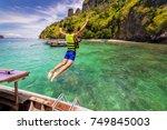 young man traveler jump into... | Shutterstock . vector #749845003