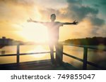 silhouette man with hands rise... | Shutterstock . vector #749855047