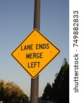 Small photo of Lane Ends Merge Left Sign