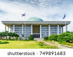 Small photo of The main view of the National Assembly Proceeding Hall at Seoul in the Republic of Korea. The building of the South Korean national government. The flag of the South Korea on the sky background.