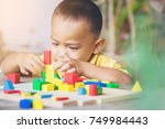 Small photo of Boy intend to build construction with weeden color blocks. concept education.