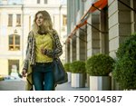 a young girl walks by the store | Shutterstock . vector #750014587