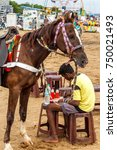 Small photo of Chennai,India,Nov 05 2017: A scene at marina beach, where a hostler or stableman eating his food during his break time, after a while managing his brown horse.