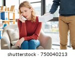 Small photo of Feeling negative. Unhappy cheerless crying woman holding a paper tissue and wiping away her tears while trying to cope with emotions
