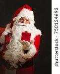santa claus holding a present ...   Shutterstock . vector #750124693
