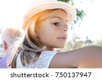 Small photo of Portrait of beautiful little bond girl wearing hat in summertime