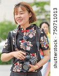 Small photo of BEIJING-MAY 4, 2016. Cheerful girl with Canon Camera. Canon is in trouble. While still renowned for top-quality cameras it is losing relevance even its consumers grow more obsessed with photography.