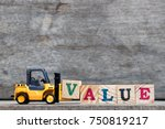 Small photo of Yellow plastic forklift hold letter V to complete word value on wood background