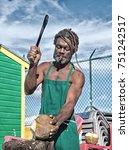 Small photo of Nassau, Bahamas - January 07, 2016: african american muscular man break big fresh raw coconut with sharp machete smoking cigar outdoor in green apron