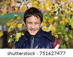 happy boy outdoors in autumn | Shutterstock . vector #751627477
