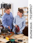 Small photo of Portrait of woodworker and pupil cutting wooden plank with fret saw in workplace at garage