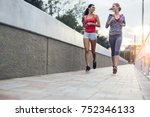 women jogging in city in dusk | Shutterstock . vector #752346133