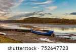 Small photo of An dilapidated boat resting on the mud flats of the River Urr in Kippford waiting for the tide to return to refloat again. The autumn colours can be seen in the trees on hills on the opposite bank
