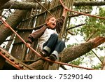 Young boy calling while climbing high tree and ropes - stock photo