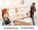 Small photo of A man and a girl add up a bookshelf for their apartment. The bookcase is made of wood. It is added by bolts. It's heavy, so they carry it together.