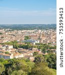 Small photo of Cityscape view of Nimes, view from ancient Roman tower (La Tour Magne), under cloudy blue sky in France
