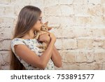 Stock photo girl with a favorite kitten young beautiful girl is holding a red kitten lovely portrait of a 753891577