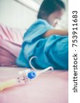 Small photo of Closeup of hand adjust iv hose for patient. Illness asian child admitted at hospital room. Girl resting on sickbed with saline intravenous (IV) drip on hand. Health care stories. Vintage film effect.