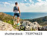 Small photo of Trail runner looking at inspirational ocean landscape from mountain peak. Accomplished man celebrate beautiful mountains and sea. Adventure and lifestyle concept.