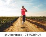 athletic woman running on rural ...   Shutterstock . vector #754025407