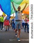 Small photo of ZAGREB, CROATIA - JUNE 11, 2016: 15th Zagreb pride. LGBTIQ activist under big rainbow flag.