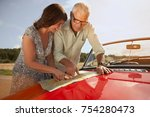 senior couple with car and map | Shutterstock . vector #754280473