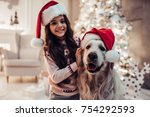 Stock photo merry christmas and happy new year charming little girl in santa claus hat with dog labrador 754292593