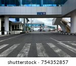 Small photo of Lombok, Indonesia. August 10, 2017. A tarmac with overhead jet bridge (jetway, gangway, aerobridge/airbridge, air jetty, portal, skybridge) or passenger boarding bridge at Lombok International Airport