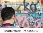 Small photo of Prague, Czech Republic - 17 August 2017: Man looking down at the photograph he just took on his Nikon DSLR in front of the John Lennon Wall in Prague on a summer day.