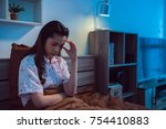 asian girl is headache in bed. | Shutterstock . vector #754410883