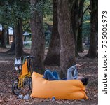 Small photo of TOKYO, JAPAN - NOVEMBER 12TH, 2017. Man lying on an air bag with smartphone in Yoyogi park in autumn